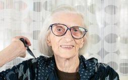 Mujer mayor que sostiene un peine Imagen de archivo libre de regalías