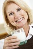 Mujer mayor que sostiene un vidrio de leche Imagen de archivo libre de regalías