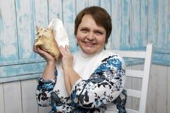 Mujer mayor que sostiene una concha marina Foco selectivo encendido Foto de archivo libre de regalías