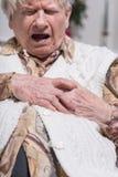 Mujer mayor que sufre de ataque del corazón imagen de archivo libre de regalías