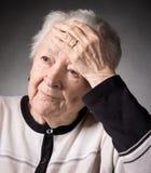 Mujer mayor que sufre de dolor de cabeza Imágenes de archivo libres de regalías
