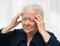 Mujer mayor que sufre de dolor de cabeza Imagen de archivo libre de regalías