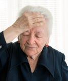 Mujer mayor que sufre de dolor de cabeza Fotos de archivo libres de regalías