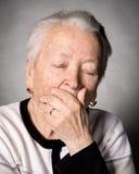 Mujer mayor que sufre de dolor de cabeza o de dolor de muelas Foto de archivo