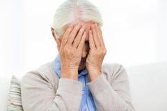 Mujer mayor que sufre de dolor de cabeza o de pena Imagen de archivo