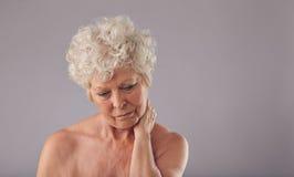 Mujer mayor que sufre de dolor de cuello Fotos de archivo