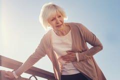 Mujer mayor que sufre de dolor en área subcostal Imagen de archivo libre de regalías