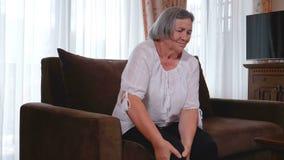 Mujer mayor que sufre de dolor en rodilla en casa almacen de video