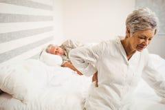 Mujer mayor que sufre del dolor de espalda que se sienta en cama Imágenes de archivo libres de regalías