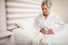 Mujer mayor que sufre del dolor de estómago que se sienta en cama imagen de archivo