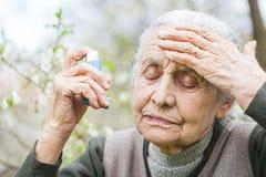Mujer mayor que tiene ataque de asma, celebrando un broncodilatador fotos de archivo libres de regalías