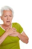 Mujer mayor que tiene ataque del corazón imagenes de archivo