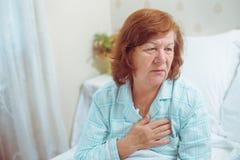 Mujer mayor que tiene ataque del corazón en casa fotos de archivo libres de regalías