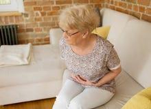 Mujer mayor que tiene dolor de estómago Foto de archivo libre de regalías