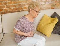 Mujer mayor que tiene dolor de estómago Fotos de archivo