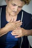 Mujer mayor que tiene dolor de pecho imagen de archivo libre de regalías
