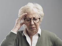 Mujer mayor que tiene un m?n dolor de cabeza imágenes de archivo libres de regalías