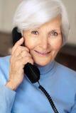 mujer mayor que tiene una llamada de teléfono Foto de archivo libre de regalías