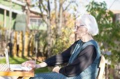 Mujer mayor que tiene una llamada video en un cuaderno Foto de archivo libre de regalías