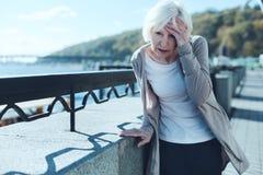 Mujer mayor que tiene vértigo al aire libre fotografía de archivo libre de regalías