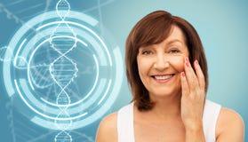 Mujer mayor que toca su cara sobre la molécula de la DNA foto de archivo