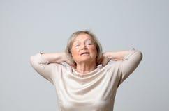 Mujer mayor que toca su cuello Imagen de archivo libre de regalías