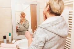 Mujer mayor que toca su piel suave de la cara, mirando en espejo en casa fotos de archivo libres de regalías