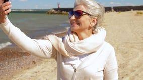 Mujer mayor que toma el selfie por smartphone en la playa metrajes