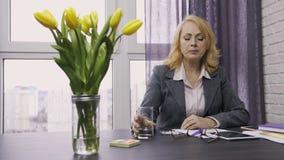 Mujer mayor que toma píldoras del dolor de cabeza en la oficina almacen de video