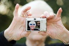 Mujer mayor que toma una fotografía del autorretrato Imagen de archivo libre de regalías