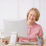 Mujer mayor que trabaja en el ordenador en el escritorio Fotos de archivo