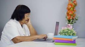 Mujer mayor que trabaja en la computadora portátil metrajes