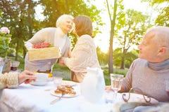 Mujer mayor que trae el regalo a la fiesta de cumpleaños fotografía de archivo