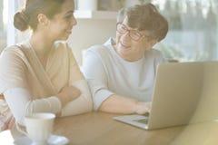 Mujer mayor que usa el ordenador portátil imagenes de archivo