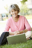 Mujer mayor que usa el ordenador portátil al aire libre fotografía de archivo