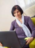 Mujer mayor que usa el ordenador portátil en casa Imagenes de archivo