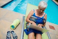Mujer mayor que usa el ordenador portátil en sillón Imagen de archivo