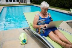 Mujer mayor que usa el ordenador portátil en sillón Foto de archivo