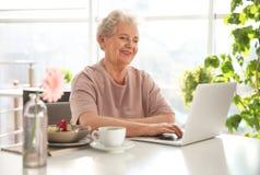 Mujer mayor que usa el ordenador portátil mientras que desayunando imagenes de archivo