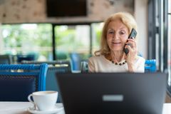 Mujer mayor que usa el ordenador portátil y el teléfono móvil fotografía de archivo