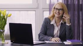Mujer mayor que usa el ordenador portátil y el teléfono móvil en el trabajo metrajes