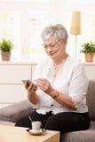 Mujer mayor que usa el palmtop fotografía de archivo