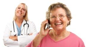 Mujer mayor que usa el teléfono celular con el doctor de sexo femenino Imagen de archivo libre de regalías