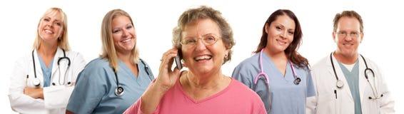 Mujer mayor que usa el teléfono celular y a los doctores Behind Imagen de archivo