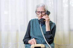 Mujer mayor que usa el teléfono dentro Foto de archivo libre de regalías