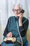 Mujer mayor que usa el teléfono dentro Imagen de archivo