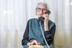 Mujer mayor que usa el teléfono dentro Imagenes de archivo