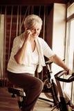 Mujer mayor que usa el teléfono elegante en el gimnasio Fotos de archivo libres de regalías