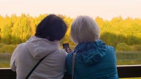 Mujer mayor que usa el teléfono elegante para el selfie móvil en la opinión de la parte posterior del paisaje del otoño almacen de metraje de vídeo