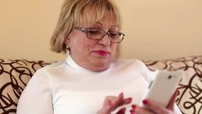 Mujer mayor que usa el teléfono móvil blanco almacen de metraje de vídeo